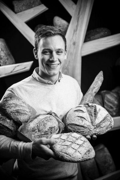 Marvin Baltus pose avecun assortiment des pains de la boulangerie 100% maison